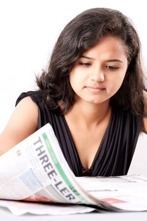 Pretty indian  woman reading newspaper isolated over white