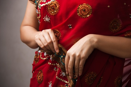 indian saree: woman wearing  beautifully embroidered red sari holding with hands  Stock Photo