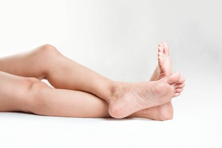 Two female  lower legs with beautiful healthy feet isolated on white background Stock Photo