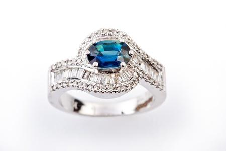 Close -up of diamond rings having big blue gem over white background