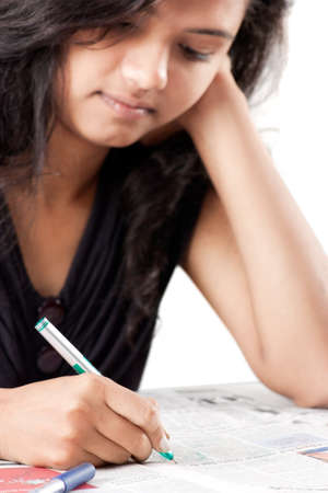 Beautiful indian girl is writing on printed newspaper with green pen photo