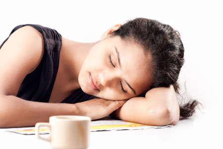 awaking: Indian girl sleeping at desk having coffee