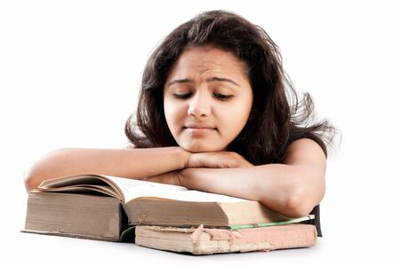 leaned: Tired and exhausted Young indian girl leaned over pile of  old books, isolated on white