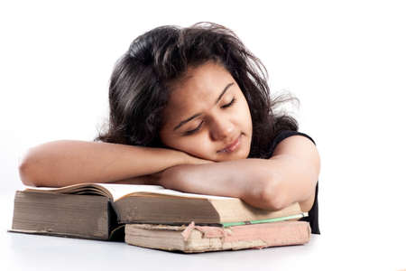 Young indian girl leaned over pile of books, isolated on white