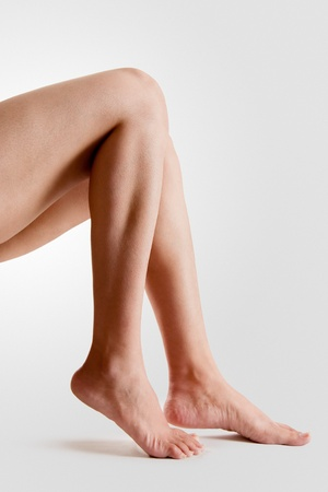 at ankle: Two female  lower legs with beautiful healthy feet isolated on white background Stock Photo