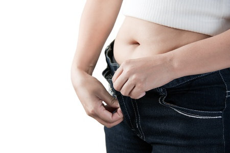 struggling: Female fatty stomach and loose jeans over white background