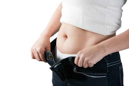 jeans apretados: Est�mago grasa femenina y pantalones sueltos sobre fondo blanco