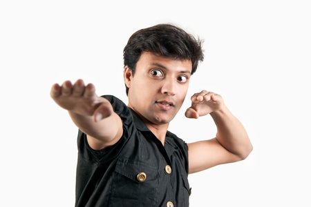 Angry Indian man in attacking position in extreme rage over white background photo