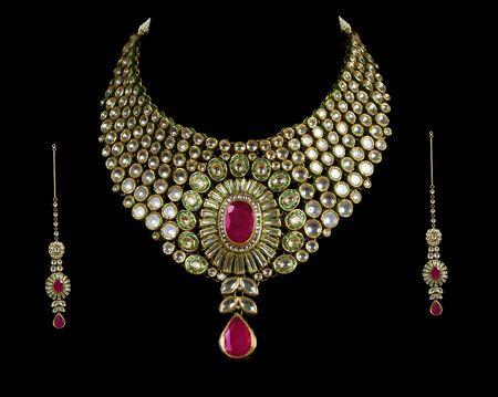 collares: Cerca de collar sobre fondo negro con anillo de diamantes oreja