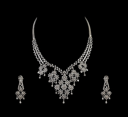 lavish: Close up of diamond necklace on black background with diamond ear ring