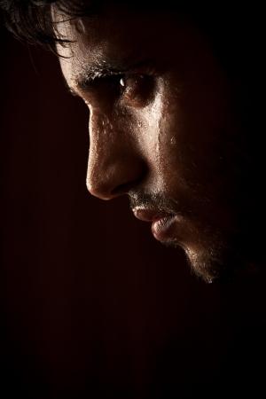 sudando: Joven indio enojado sudor sobre la oscuridad