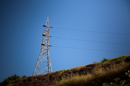 Electricity pylon with grid power under blue sky on hill Stock Photo - 14306380