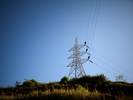 utilities: Electricity pylon with grid power under blue sky on hill  Stock Photo