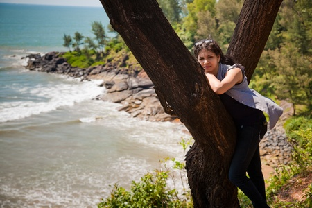 Happy Beautiful Indian girl resting over tree trunk and blue ocean and beach as natural background photo