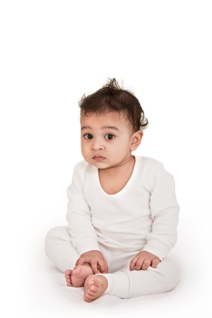 Adorable Indian baby playing with over white background photo
