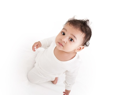 Adorable Indian baby playing with over white background