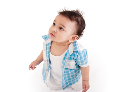 Adorable Indian baby standing and looking over white background Stock Photo
