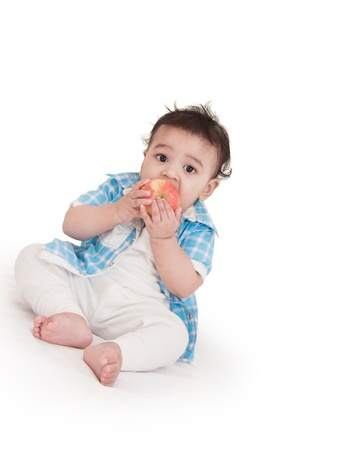 Adorable Indian baby eating apple over white background photo