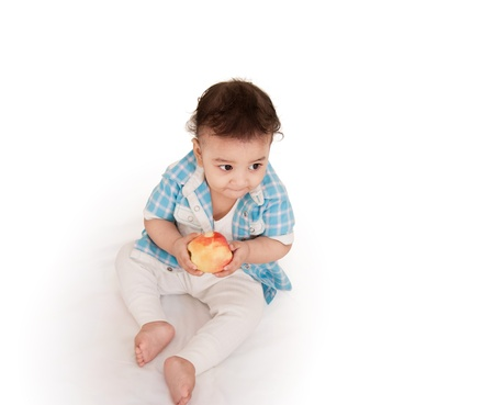 over eating: Adorable Indian baby eating apple over white background