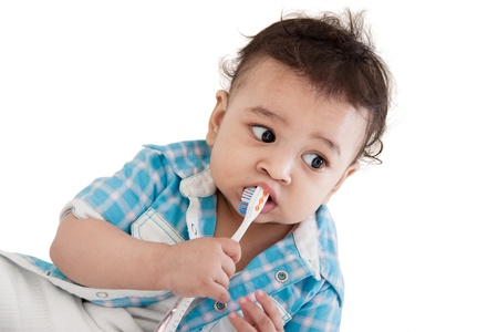 tooth brush: Adorable Indian baby brushing teeth over white background