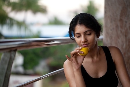Happy Indian beautiful girl with coffee cup photo