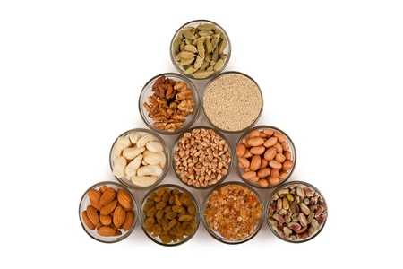 Pile of mix collection of dry fruits in glass bowl isolated over white Stock Photo