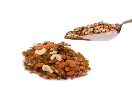 Pile of mix collection of dry fruits falling from steel spoon isolated over white photo