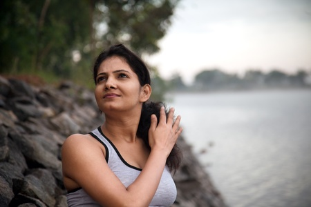 Happy indian girl on morning relaxing after exercise or jogging very near to lake photo