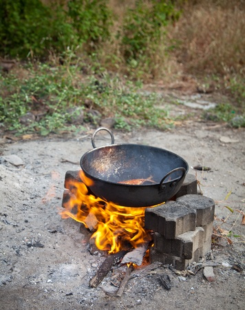 Cooking three fresh water fish in oil on open fire Stock Photo - 12295527