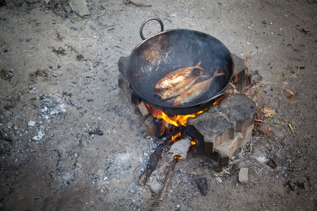 Cooking three fresh water fish in oil on open fire Stock Photo - 12295525