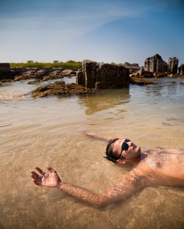Indian man swimming at ocean beach with sunglasses photo