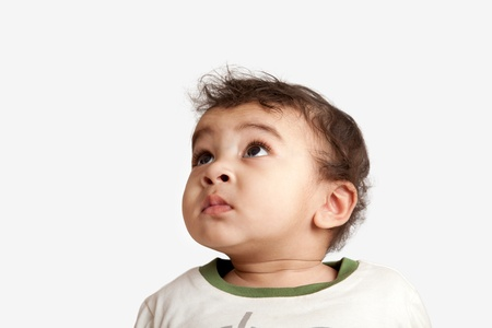 indian curious boy baby looking at the camera on white background. photo