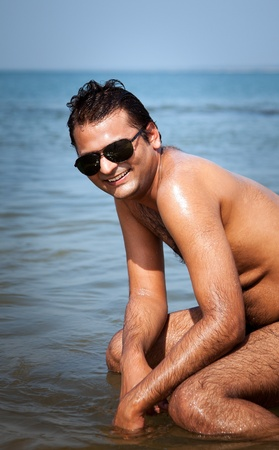 Indian Happy young man getting out of the water with sunglasses photo