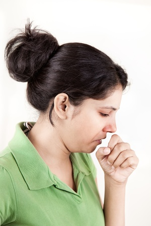 Indian girl with a cold coughing over white background feeling pain