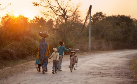 Indian women coming back to home in sari after finishing work in village with some bag on her head in noon