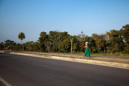 Beautiful view of road side trees blue sky woman traveling on footpath photo
