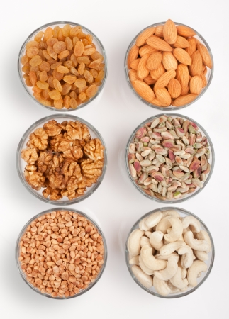 frutas secas: Pila de recogida de mezcla de frutos secos en un taz�n de vidrio sobre blanco