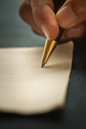 hombre escribiendo: Close-up shot de la mano de un hombre s, sosteniendo una pluma Foto de archivo