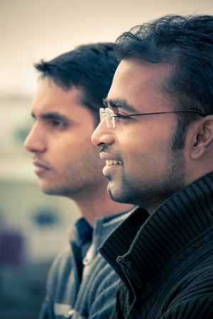 Two indian happy handsome men looking at something and both are smiling  photo