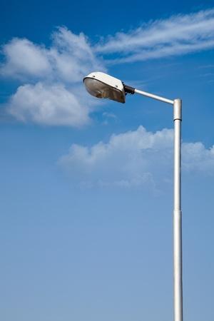 deter: Pole of street lite under blue sky in sunlight