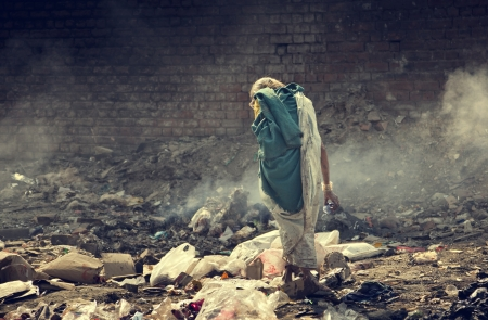 Pollution and poverty   Indian old female searching food for herself in  garbage,