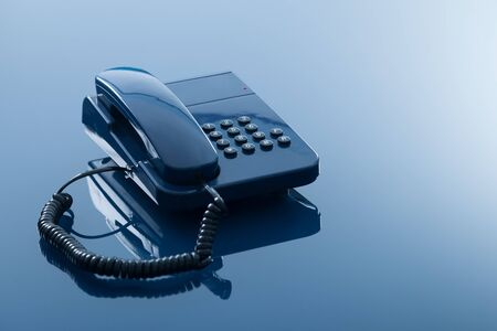 Old fashioned telephone  with reflection isolated on transparent blue background  photo