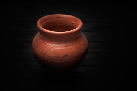 pot light: Close-up of soft clay pot over gray background