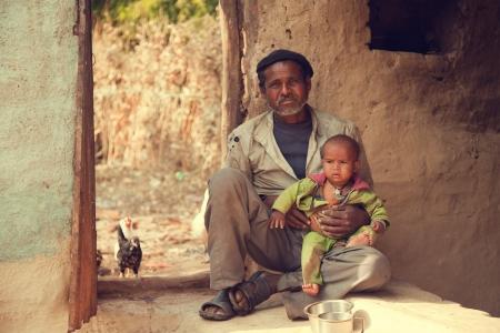 hombre pobre: Padre pobre indio y su hijo sentado en el suelo y él está sosteniendo a su hijo Foto de archivo