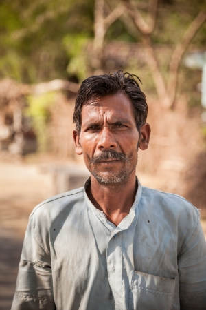 Close-up of an old face of Indian villager man having wrinkle but smile on face photo