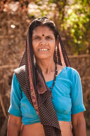 Middle age indian villager woman with dark complexion  looking at camera photo