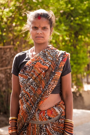 burdened: Indian happy villager woman  standing , looking at camera