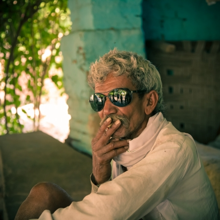 cigar smoking man: Portrait  of indian villager  while smoking with a rural cigar along intense having sunglasses