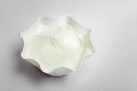 Dairy milk powder in bowl isolated over white photo