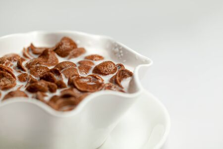 A bowl of chocolate  Corn flakes with milk isolated over white background photo